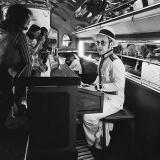 Элтон Джон в пиано-баре на борту своего частного самолета – 1976 год