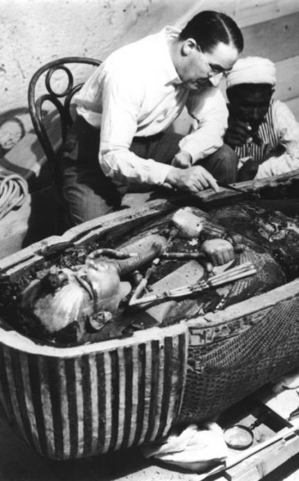 Говард Картер, английский археолог, рассматривает открытый саркофаг Тутанхамона