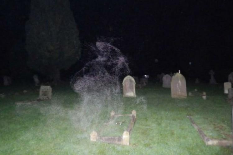 Фотография призрака женщины в капюшоне на кладбище